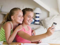 Young Girls Distracted From Their Homework, Playing With A Cellphone - stock photo
