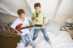 Two Boys Standing On A Bed, Playing Guitar And Singing Into A Hairbrush Stock Photos