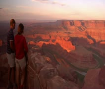 A couple watches the sunrise at dead horse point State Park Utah Stock Footage