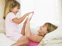 Stock Photo of Young Girl Being Woken Up By Her Little Sister