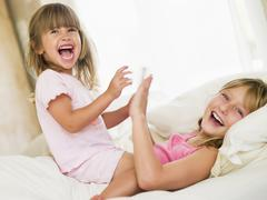 Young Girl Being Woken Up By Her Little Sister - stock photo