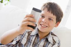 Young Boy Sitting On A Sofa Texting On A Mobile Phone Stock Photos