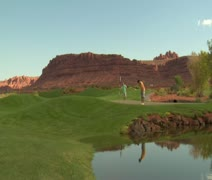 Father and son putt on golf course with pond and red rock cliffs Stock Footage