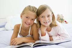 Two Young Girls In Their Pajamas, Reading A Book - stock photo