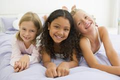 Three Young Girls Lying On A Bed In Their Pajamas - stock photo