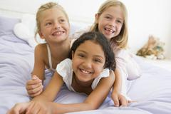 Three Young Girls Lying On Top Of Each Other In Their Pajamas Stock Photos
