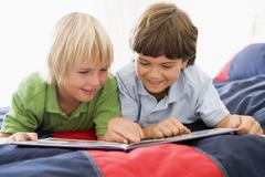 Two Young Boys Lying Down On A Bed Reading A Book Stock Photos