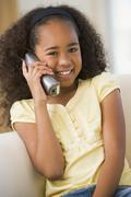 Young Girl Sitting On A Sofa, Talking On A Telephone Stock Photos
