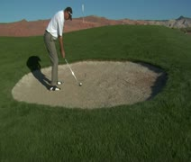 Jib  shot of man hitting a golf ball from sand trap Stock Footage