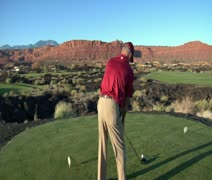 Slow-motion  steadicam shot of man teeing off on golf course with sunset and red Stock Footage