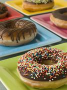 Selection Of Ring Doughnuts On A Different Coloured Plates Stock Photos