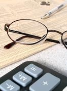 reading glasses resting on finacial newspaper with calculator in foreground - stock photo
