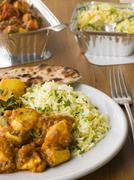 Plate Of Indian Take Away- Chicken Bhoona, Sag Aloo, Pilau Rice And Naan Bread Stock Photos