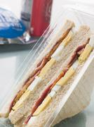 Egg And Bacon Sandwich On White Bread With A Bag Of Crisps And A Can Of Fizzy Stock Photos