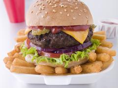 Cheese Burger In A Sesame Seed Bun With Fries Stock Photos