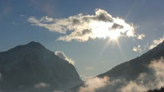 Sun shines from behind a cloud between two mountains - stock footage