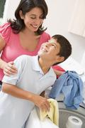 Mother and son doing laundry Stock Photos