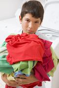 young boy holding a pile of laundry - stock photo