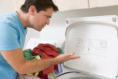 Man doing laundry Stock Photos