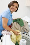 Woman loading washing machine Stock Photos