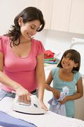 Mother and daughter ironing Stock Photos