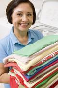 Woman holding folded laundry Stock Photos