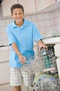 young boy loading dishwasher - stock photo
