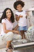 Mother and daughter loading dishwasher Stock Photos
