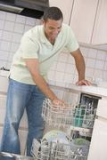 man loading dishwasher - stock photo