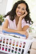 Woman leaning on washing in basket Stock Photos