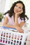 woman daydreaming over washing basket - stock photo