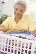 Woman leaning on washing basket Stock Photos