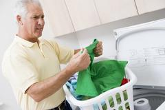 man reading washing instructions - stock photo