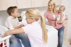 mother and children doing laundry - stock photo