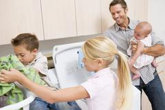 Father and children doing laundry Stock Photos