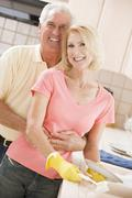 husband and wife cleaning dishes - stock photo