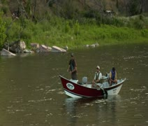 Pullout shot of flyfishing drift boat in calm river Stock Footage