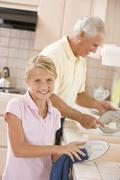 grandfather and granddaughter cleaning dishes together - stock photo
