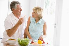 Stock Photo of husband and wife preparing meal,mealtime together
