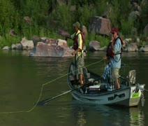 Slow-motion shot of fly fishing drift boat passing camera Stock Footage