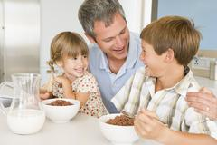 father sitting with children as they eat breakfast - stock photo