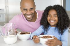 Father sitting with daughter as she they eat breakfast Stock Photos