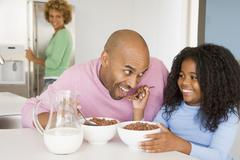 father sitting with daughter as she they eat breakfast with her - stock photo