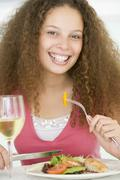 Stock Photo of woman eating meal,mealtime with a glass of wine