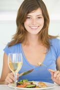 Young woman enjoying meal,mealtime with a glass of wine Stock Photos