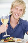 young man enjoying meal,mealtime with a glass of wine - stock photo