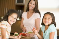 Girls eating pepper strips while mother is preparing meal,mealti Stock Photos