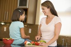 mother and daughter preparing meal,mealtime together - stock photo