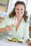 Stock Photo of woman enjoying meal,mealtime with a glass of wine