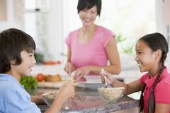 Children enjoying breakfast while mother is preparing food Stock Photos